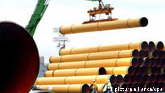 Yellow pipes being lifted into the air by a crane