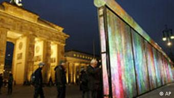 Tourists look at the installation 'Vanished Berlin Wall' by South Korean artist Eun Sok Lee on the eve of the 18th anniversary of the opening of the Berlin Wall in front of the Brandenburg Gate
