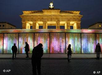 Tourists look at the installation 'Vanished Berlin Wall' by South Korean artist Eun Sok Lee on the eve of the 18th anniversary of the opening of the Berlin Wall