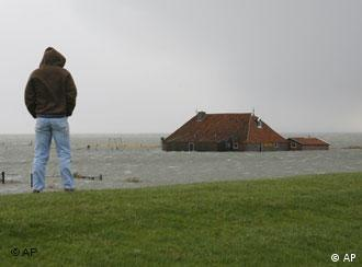 A person looks at a flooded farmhouse on a Dutch island