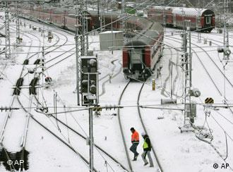 Railway workers walk through snow and past idle commuter trains at the central station in Munich