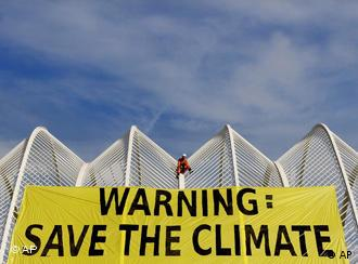 Greenpeace members display a giant banner reading Warning: Save the Climate at the opening of the IPCC conference, which finished Saturday, Nov. 17