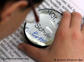 A student a school for visually impaired looks through a magnifying glass at a text