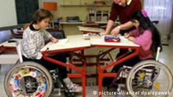Two students in wheelchairs at a school desks