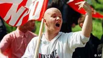 A man wearing a grey sweatshirt and holding a red NPD flag screams and raises his hand in the air.