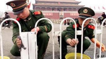 Chinesische Polizisten putzen einen Zaun vor dem Tor des himmlischen Friedens