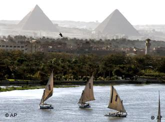 Boats on the river Nile, the pyramids in the background