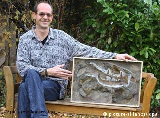 Scientist Markus Poschmann sits outside, holding the giant scorpion claw he excavated