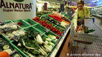 A woman stops with her shopping cart in front of a table full of fresh fruits and vegetables.
