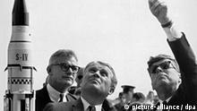 Wernher von Braun (l), Direktor des Marshall Space Flight Center (MSFC), erklärt dem amerikanischen Präsidenten John F. Kennedy (r) am 16.11.1963 im Raumfahrtzentrum Cape Canaveral in Florida das System der Saturn Trägerraketen. Links hinter von Braun der stellvertretende Nasa-Geschäftsführer Robert Seamans. Kennedy fiel am 22.11.1963 in Dallas (Texas) einem Attentat zum Opfer.