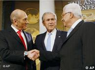 Ehud Olmert and Mahmoud Abbas shake hands as George W. Bush looks on