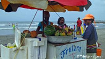 A woman sells fruit from a stand on the beach in Cartagena, Colombia