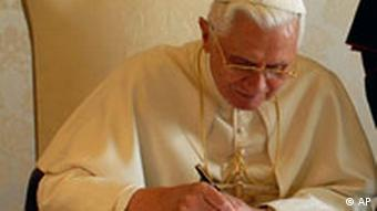 Pope Benedict XVI signs a document