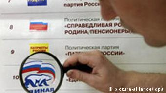 A man looks through a loupe at the logo of the pro-presidential party United Russia showed among others on the election poster