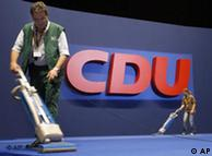 People vacuum the floor in front of a CDU logo