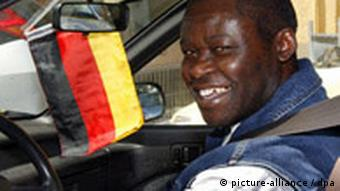 A Ugandan immigrant with German citizenship drives his car through Berlin with a German flag hanging from the rear-view mirror