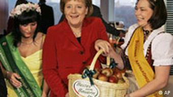 Merkel holding a bakset of apples