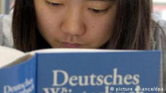 A woman looks through a German dictionary