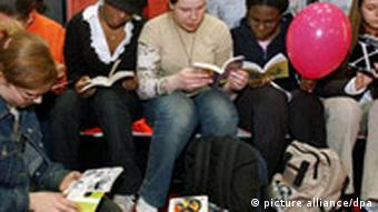Teenage women reading books on the floor of the Leipzig Book Fair.