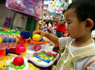 A young boy plays with plastic toys