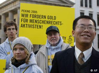Biao Teng, chinesischer Anwalt und Menschenrechtsaktivist, rechts, nimmt am Freitag, 7. Dez. 2007, vor dem Brandenburger Tor in Berlin an einer Demonstration von amnesty international teil. Zum Internationalen Tag der Menschenrechte am 10. Dezember 2007, will amnesty international China daran daran erinnern, im Zusammenhang mit den Olympischen Spielen 2008 in Peking die Lage der Menschenrechte zu verbessern. (AP Photo/Franka Bruns) ---Biao Teng, Chinese lawyer and human rights activist, right, demonstrates with other amnesty international protestors in front of the Brandenburg Gate in Berlin, Friday, 7. Dec. 2007. Amnesty international wanted to remind China to improve human rights in regard to the Olympic Games in Beijing in 2008. The sign says: Beijing 2008: We are asking Gold for human rights activists. (AP Photo/Franka Bruns)
