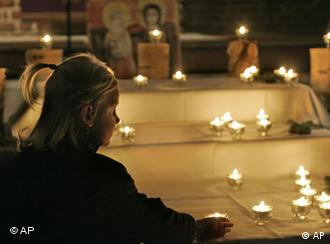 Ein Mädchen stellt zu Beginn des Trauergottesdienst für die getöteten Kinder von Darry eine Kerze auf