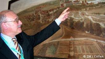 Gerhard Albert przed starym obrazem przedstawiającym Wzgórze Kategralne.