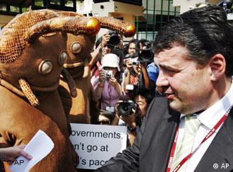 Sigmar Gabriel is interviewed as environmental activists dressed as snails stand nearby