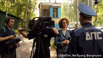 Irene Langemann (center right) and her camera crew talk with a Russian police officer