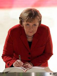 German Chancellor Angela Merkel signs the EU's Treaty of Lisbon during a ceremony Thursday, Dec. 13 2007