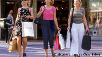 Three women walk out of a department store carrying shopping bags