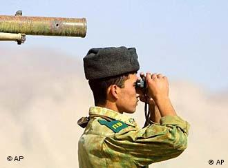 A Russian soldier uses binoculars to look across the Afghan border