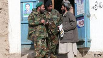 NATO troops speak with an Afghan man