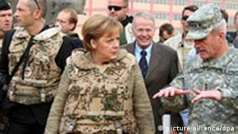 Angela Merkel, left, speaks with General Dan McNeill, right