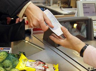 A person handing a euro note to a cashier