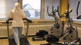 Muslim woman on treadmill at Hayat fitness club in Cologne