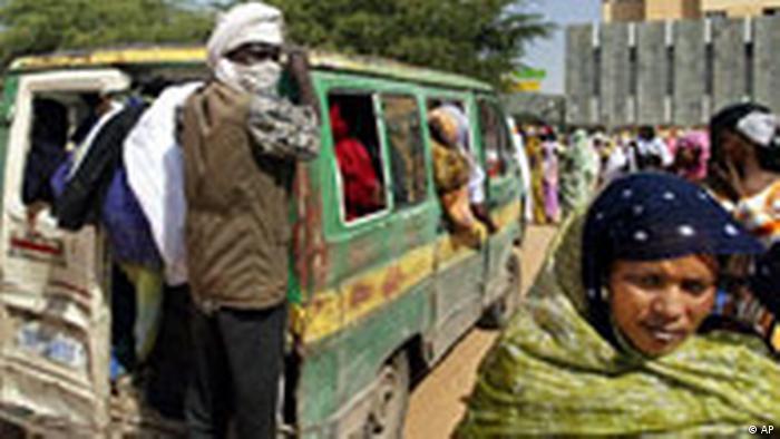 Улична сцена от Нуакшот, Мавритания: препълнен микробус лавира между пешеходци