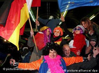 People in costumes celebrate at the German-Polish border