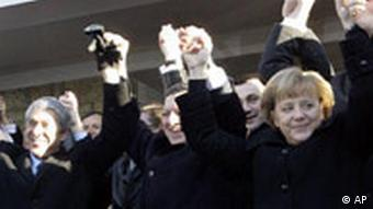 European leaders, clad in black coats, link arms and cheer
