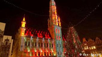 The spires of an old city hall building are lit by thousands of Christmas lights with a Christmas tree dominating the square (Photo: Xinhua (c) dpa)
