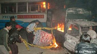Supporters of Bhutto burn a police vehicle and a bus after Bhutto's murder
