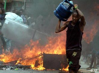 A man running across the road holding a looted gas cylinder from a shop in Mombasa, Kenya, with fire in background