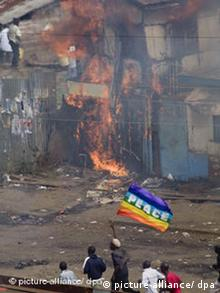 Slum dwellers run waving a flag with peace written on it next to a burning house in a Nairobi slum
