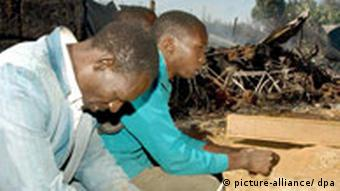 Two men weep outside a church where 46 people were burned to death in 2008
