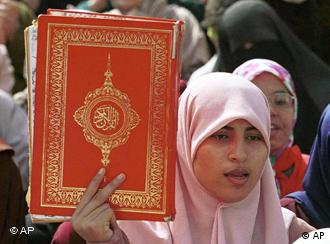 A woman in a pink headscarf holds a large Koran