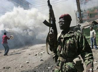 A police officer walks past burning buildings in Nairobi