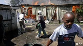 Residents attempt to put out a fire in shops allegedly set by the opposition leader Raila Odinga supporters, in Nairobi, January 2007.