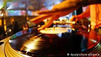 A DJ spins a record on a turntable