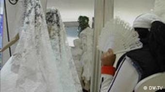 A German-born Turk - again, not Sibel - chooses her wedding dress, obscuring her face with a fan