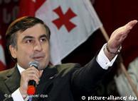 President Mikhail Saakashvili stands in front of Georgian flag